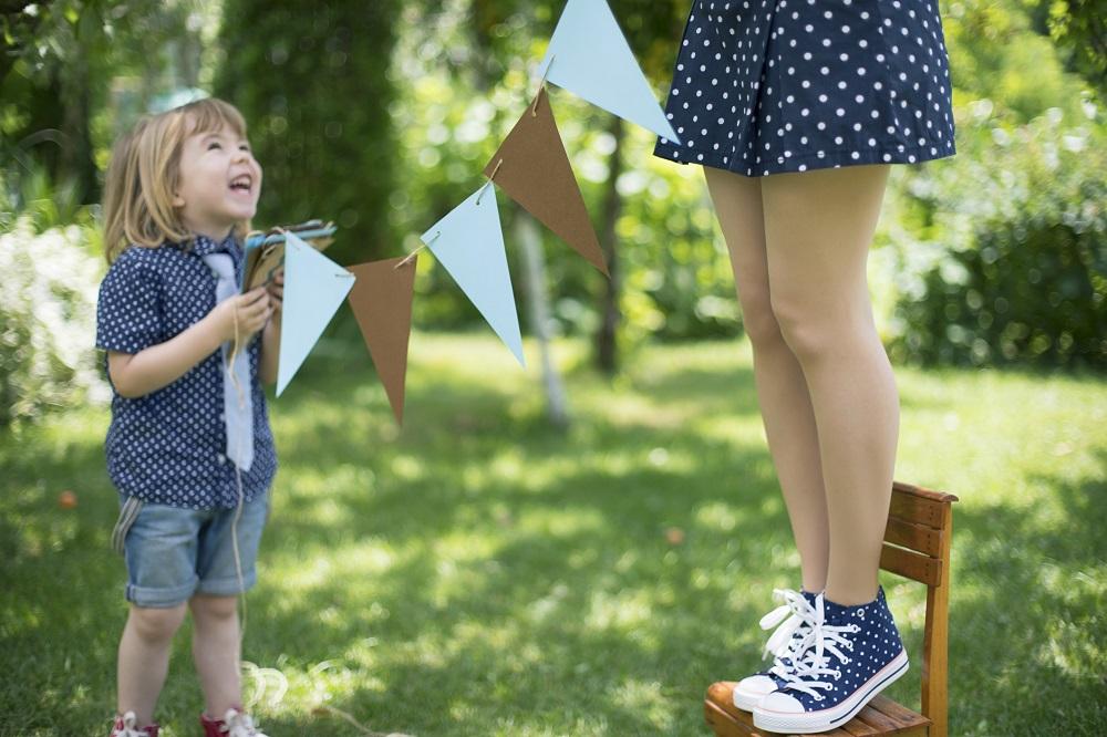 Kind und Mutter dekorieren für die Gartenparty