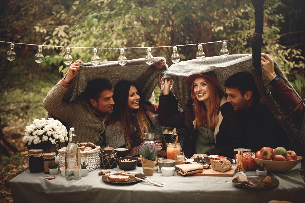 Partygäste schützen sich mit Decken vor Regen
