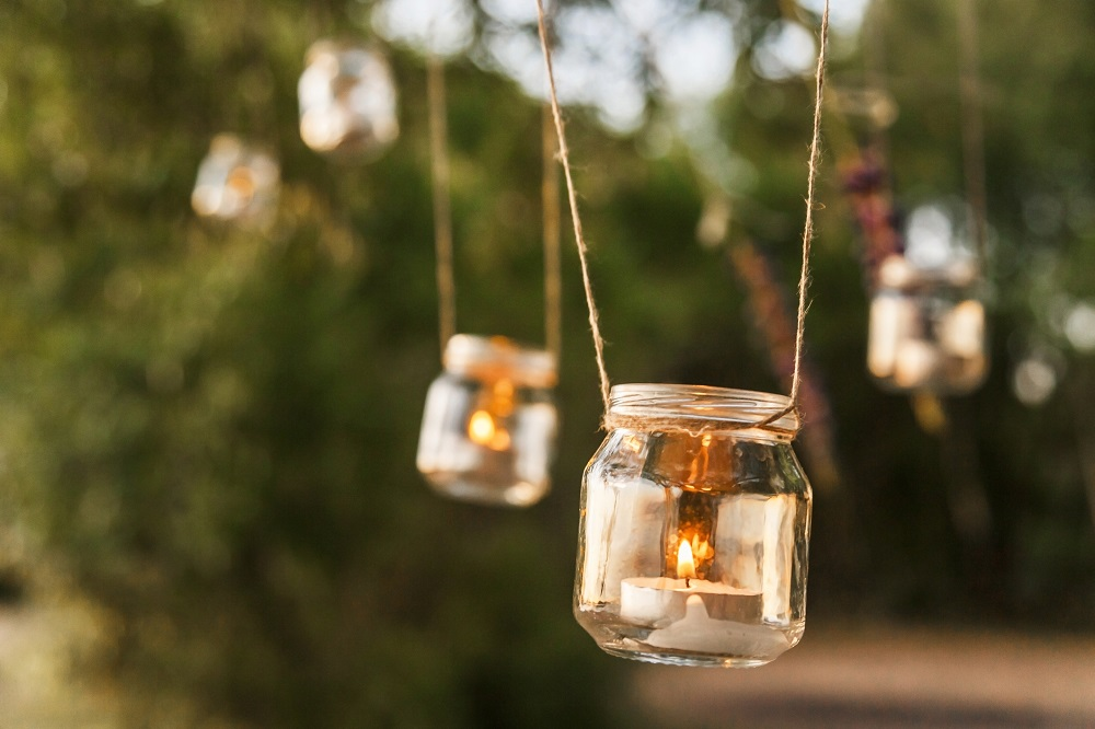 Einmachgläser mit Teelichtern im Garten aufhängen