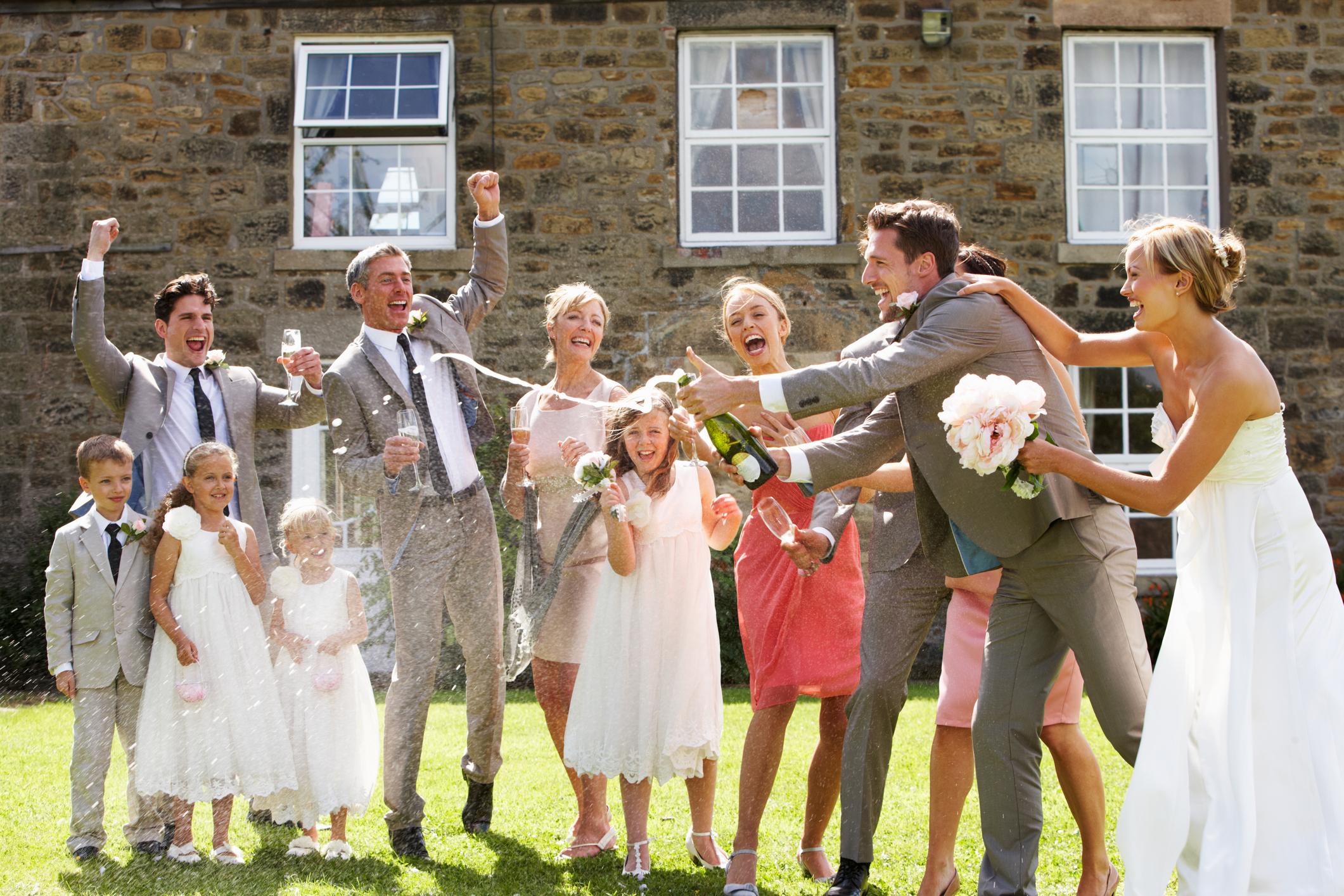 Hochzeitsgesellschaft mit Brautpaar beim Sektempfang