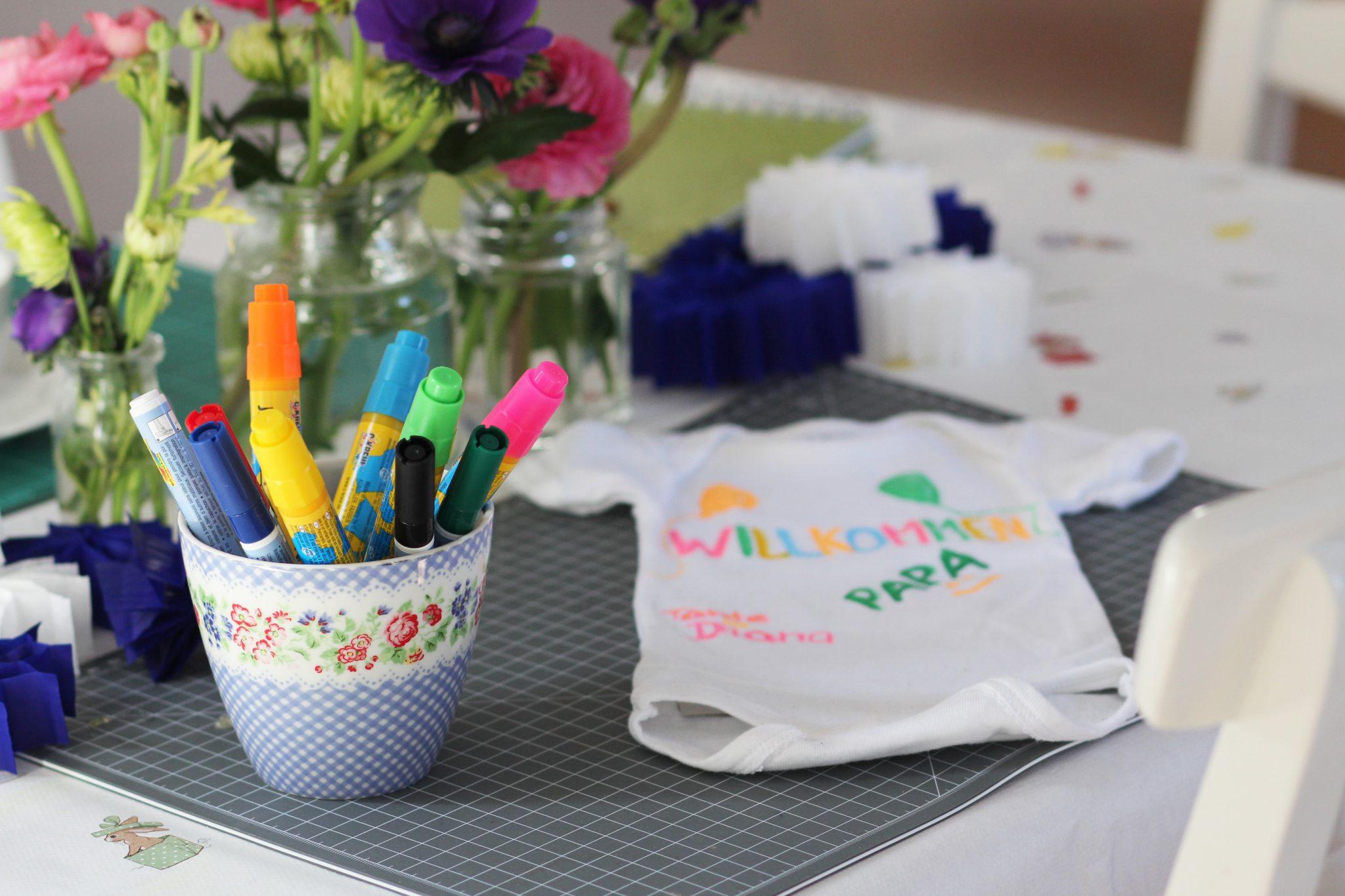 Basteltisch auf einer Babyparty mit Strampler und Textilmalstiften
