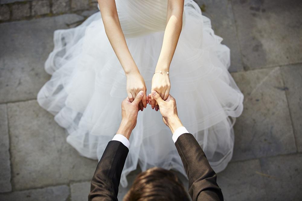 Brautpaar hält sich an den Händen