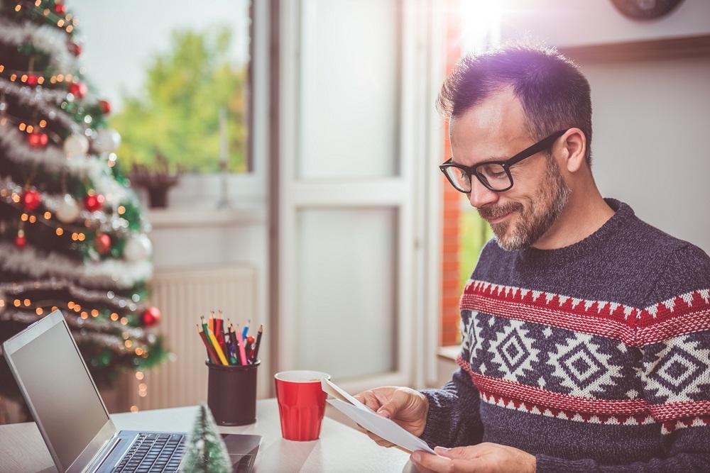 Mann bereitet Weihnachtskarte vor.