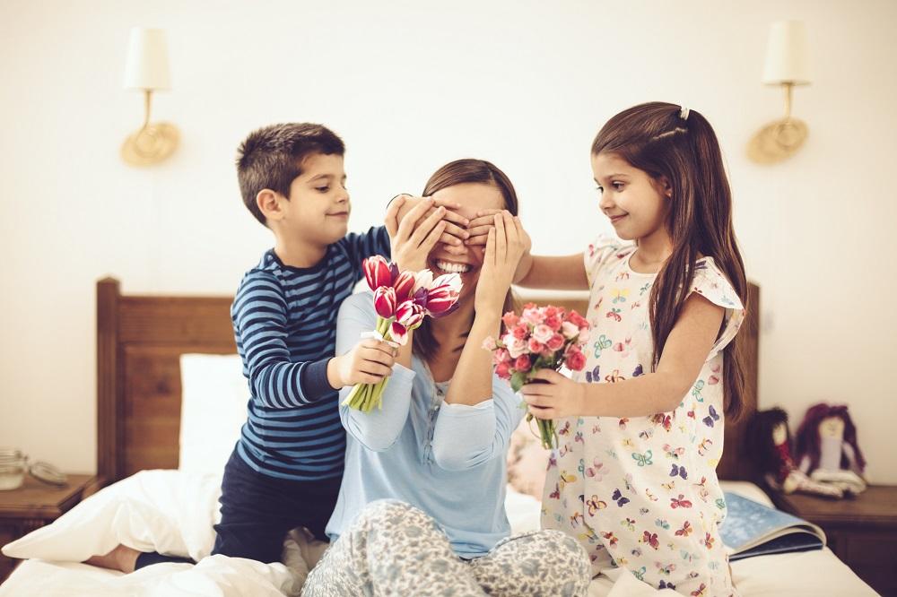 Kinder überraschen ihre Mama mit Blumen.