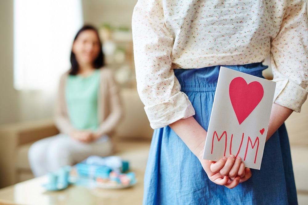 Kind schenkt seiner Mama eine selbstgebastelte Karte.
