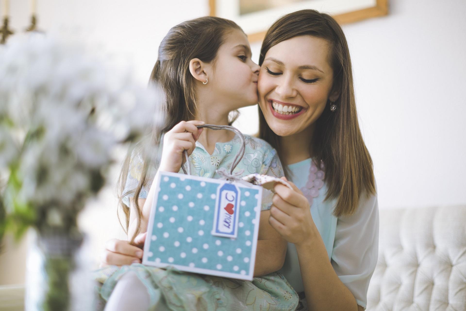 Alt-Tag: Kind übergibt ihrer Mama ein Geschenk zum Muttertag.