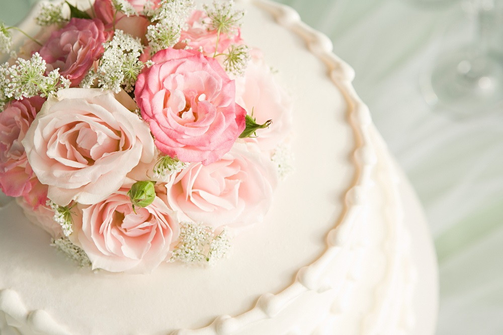 weiße Fondant-Hochzeitstorte mit rosa Blumentopping