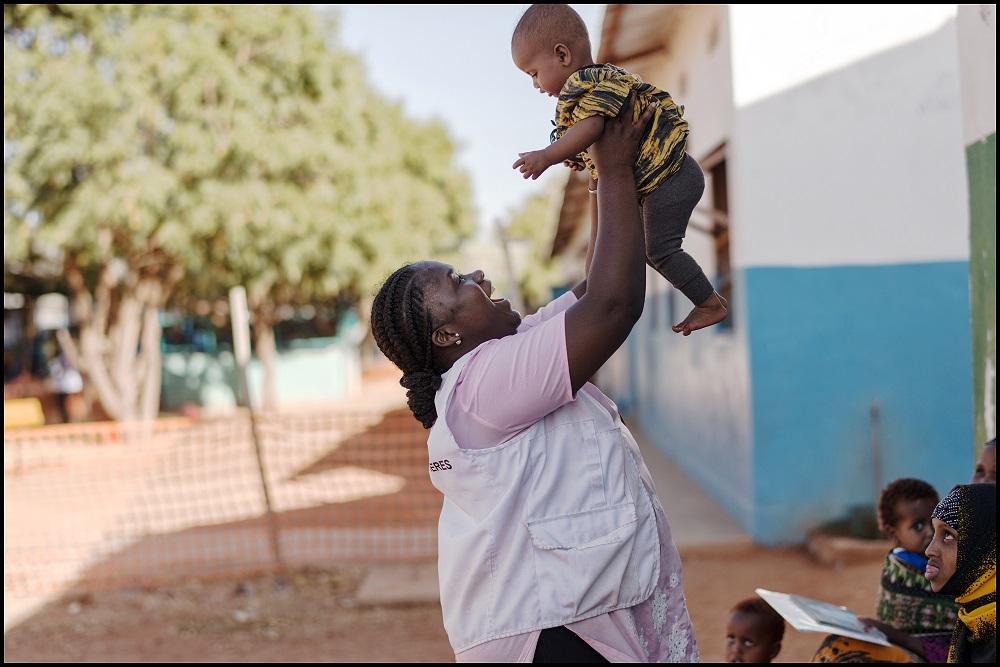 Mitarbeiterin von Ärzte ohne Grenzen spielt mit Baby