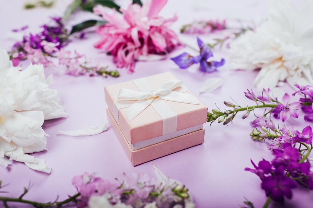 Geschenk zwischen lilafarbenen Blumen