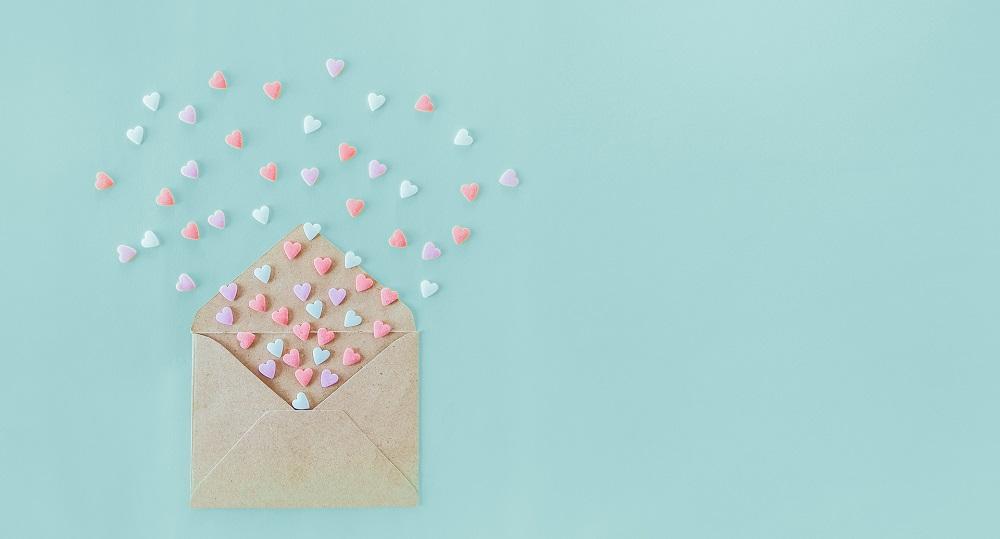 Glückwünsche zur Hochzeit fliegen wie kleine Herzen aus Briefumschlag