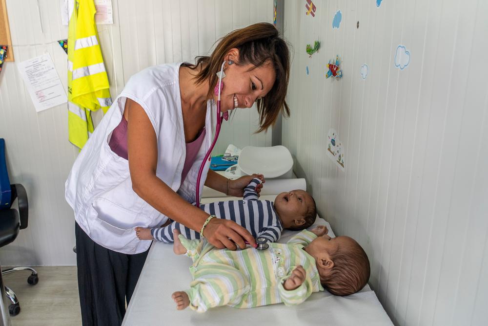 Mitarbeiterin von Ärzte ohne Grenzen untersucht Babys