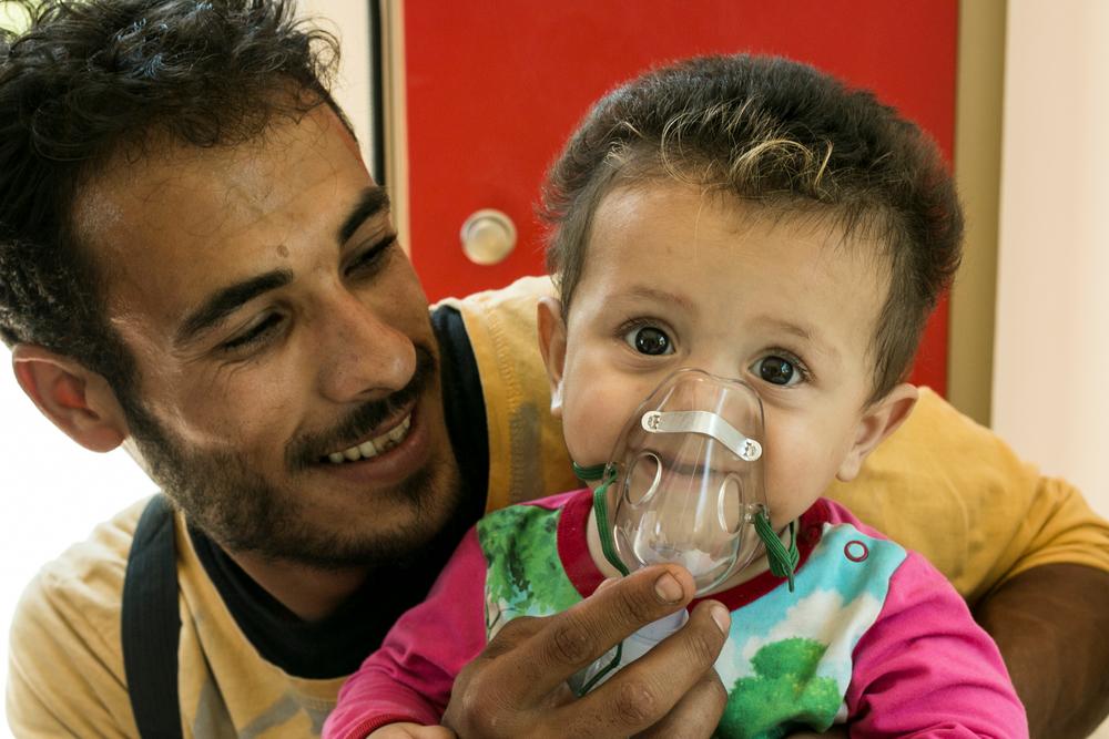 Mann und Baby mit Atemgerät