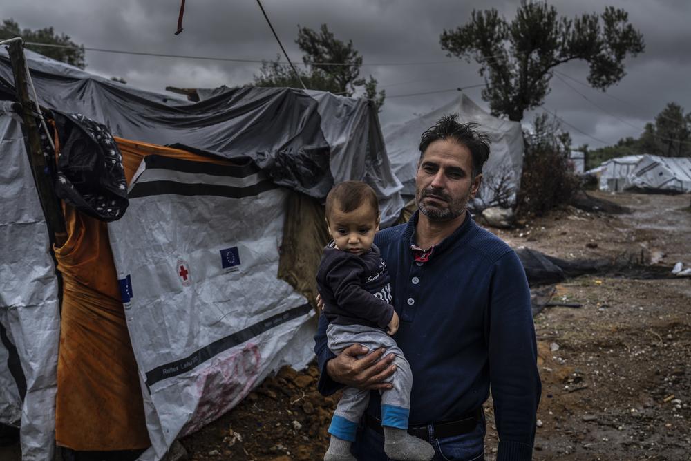 Mann mit Baby in Flüchtlingslager