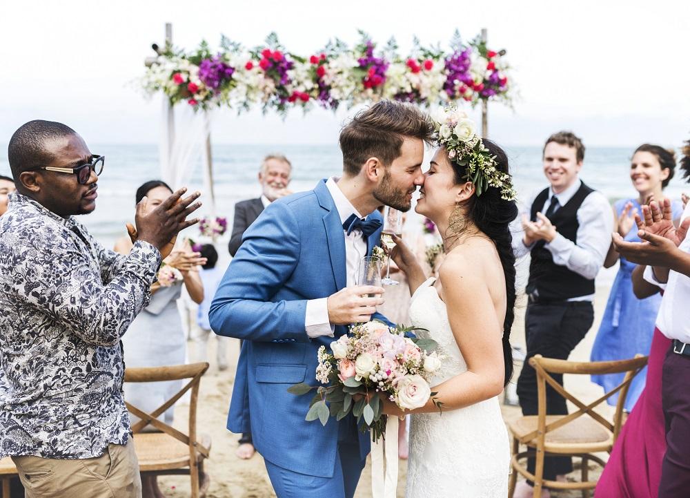Sich küssendes Hochzeitspaar als Symbolbild für Hochzeitseinladungen, die das Motto der Hochzeit aufgreifen