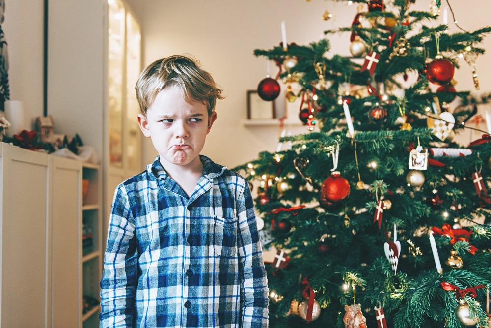 Kind schaut grimmig fürs Weihnachtsfoto