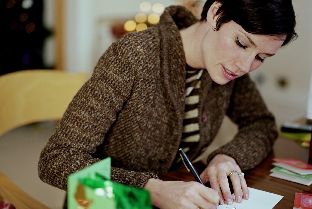 Frau schreibt geschäftliche Weihnachtskarte um danke zu sagen