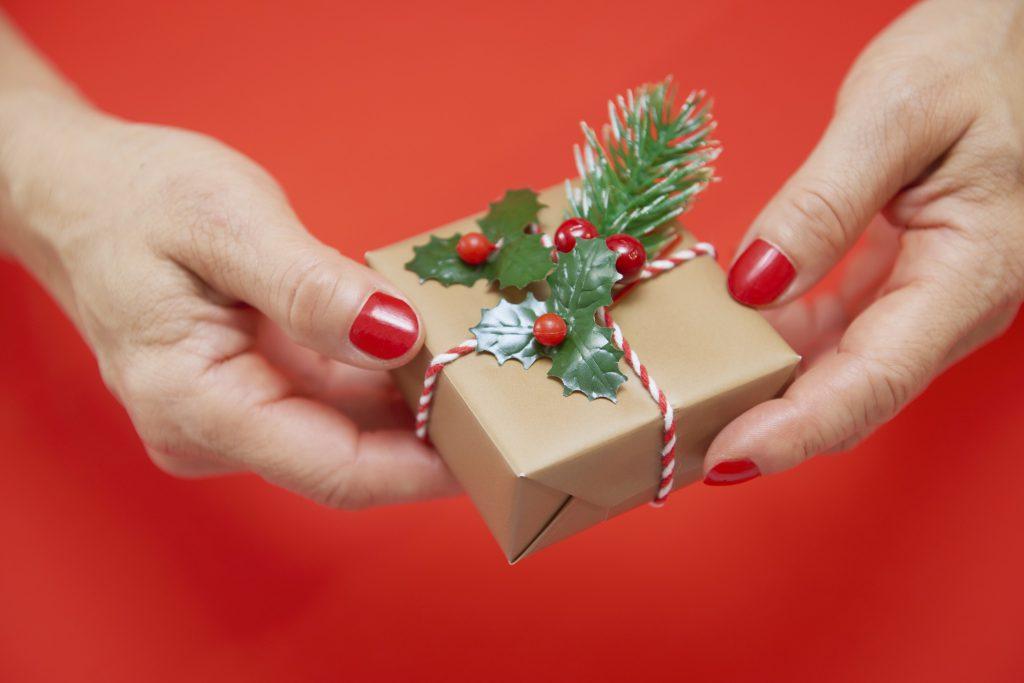 Frau überreicht geschäftliches Weihnachtsgeschenk