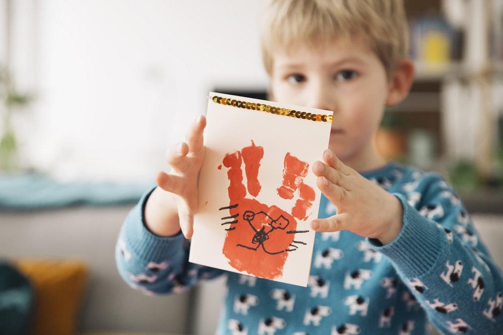 : Kind mit selbstgemalter Osterkarte