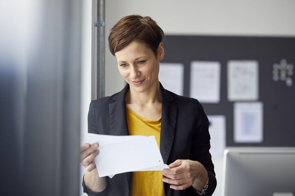 Frau liest geschäftlichen Brief mit korrekter Anrede