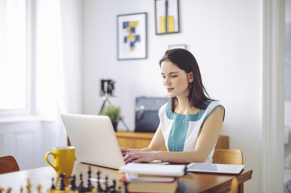 Frau im Home Office schreibt geschäftlichen Brief