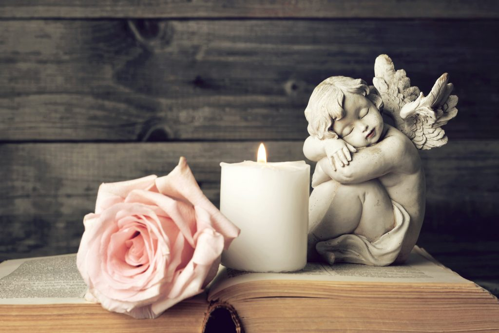 Trauersprüche: Engel, Kerze und eine Rose spenden Trost