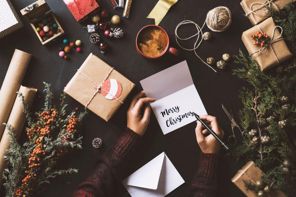 Frau schreibt Adventsgrüße auf eine Karte