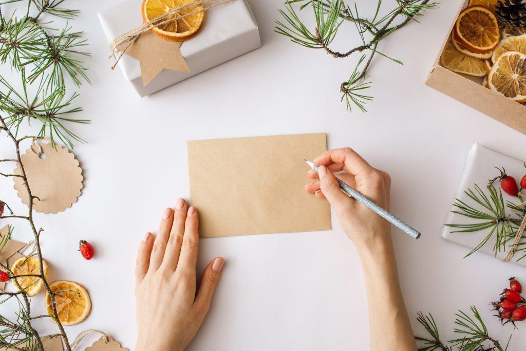 Weihnachtspost schreiben am Tisch mit Geschenken