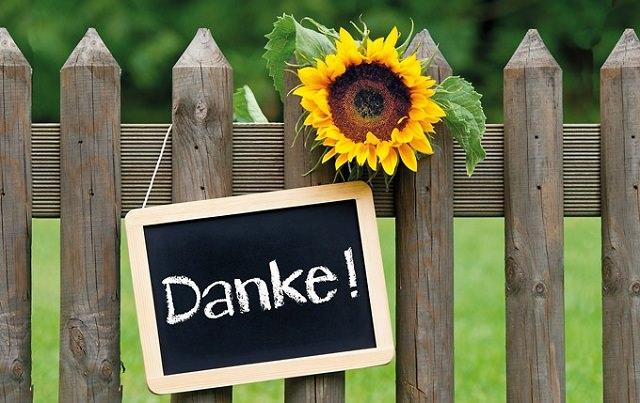 """Schiefertafel mit Aufschrift """"Danke"""" über einem Gartenzaun hängend."""