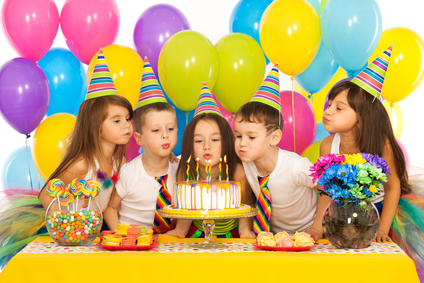Kinder pusten Kerzen auf einer Torte aus