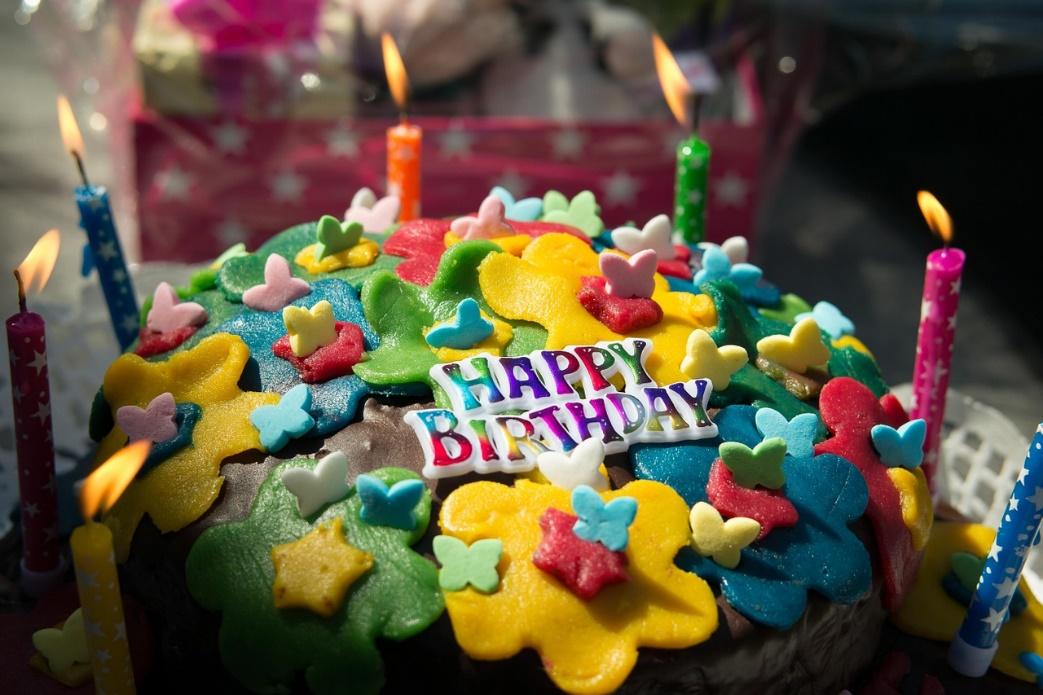 Torte mit Kerzen und Aufschrift Happy Birthday