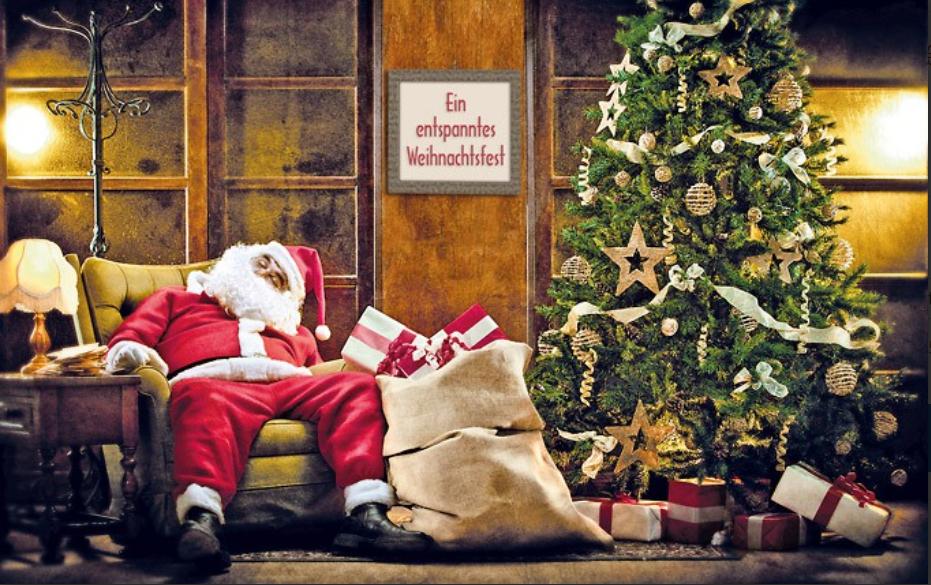 Weihnachtsmann schläft auf dem Sofa neben dem Weihnachtsbaum